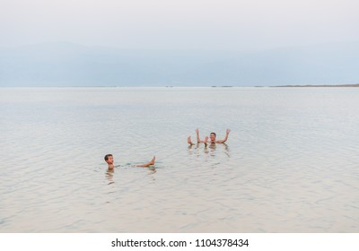 Mother and son relaxing on a surface of dead sea water. Summer vacation holiday health care concept