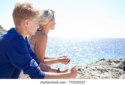 Mother and son relaxing together, leaning on wooden banister, contemplating the blue sea on sunny holiday destination beach, outdoors. Family mum and teenager enjoying travel recreation lifestyle.