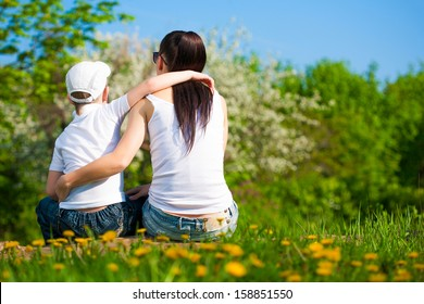 mother and son are resting in the park. summer