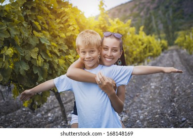 mother and son are resting in the vineyard. summer
