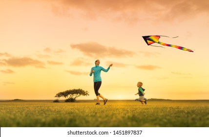 Mother and son running together flying a kite, having fun outdoors.