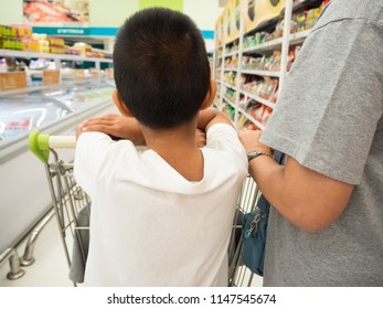 Mother and son with shopping cart choose fresh food in the supermarket.