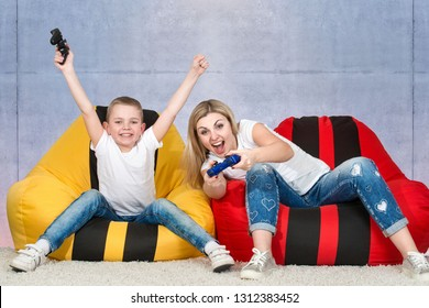 Mother and son sit on chairs bags and play video games .Emotions.