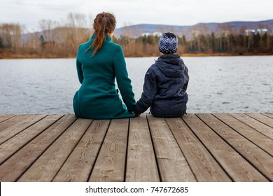 mother and son sit side by side on the pier by the pond
