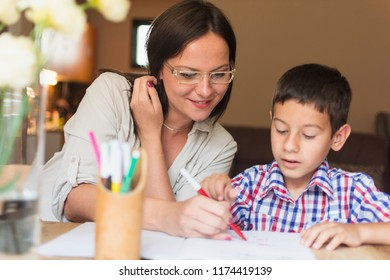 The mother and son sit at the table and paint together. The mother helps her son to choose the appropriate colors for his homework. Mother assistance in the drawing and coloring of the homework.