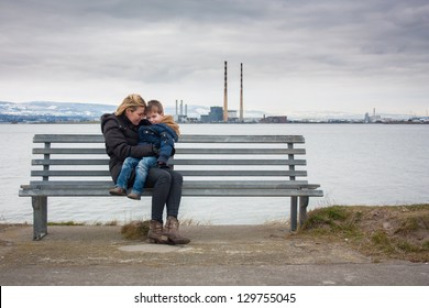 Mother and son sitting on bench with industrial backdrop