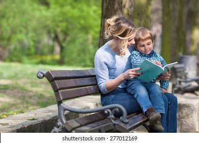 Mother and son sitting on a bench in a park and reading a book