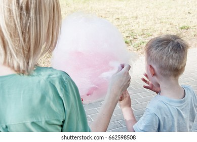 Mother and son are sitting on a bench in the park and eating sweet cotton wool.