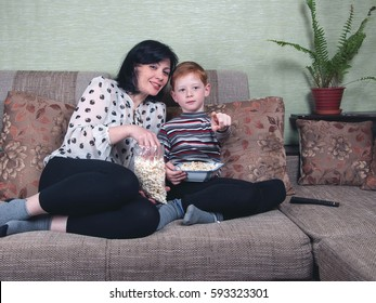 Mother and son sitting on the couch, watching a Comedy on TV, eating popcorn.