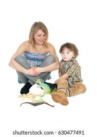 A mother and son sitting on the floor playing with his toy dinosaurs,