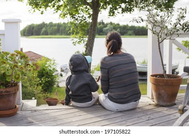 Mother with son sitting on porch and looking at water