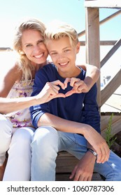 Mother and son sitting on wood steps hugging looking smiling, enjoying day out activities outdoors. Family enjoying loving closeness, mom with hands in heart shape, travel leisure recreation lifestyle