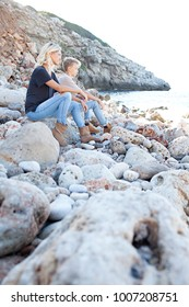 Mother and son sitting together on rocky beach on summer holiday, contemplating the sea sharing enjoying nature, outdoors. Mum and teenager child travel wellness recreation lifestyle, family exterior