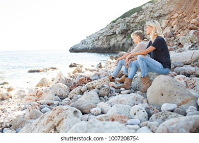 Mother and son sitting together on rocky beach on summer holiday, contemplating the sea, healthy outdoors. Mum and teenager child travel wellness recreation lifestyle, family in exterior.