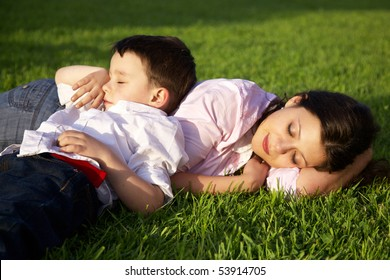 mother and son sleeping on grass