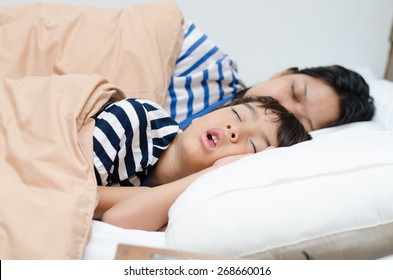 Mother with son sleeping together in bedroom