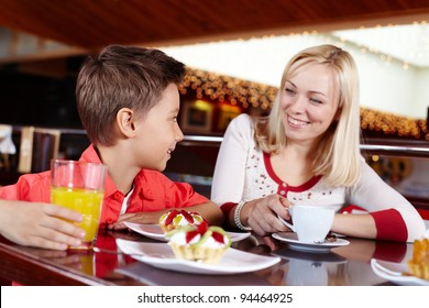 Mother and son spending time together eating delicious desserts