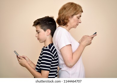 Mother and son standing back to back, holding their smartphones in hands, seriously looking at screens. They are ignoring each other. Family and modern technology addiction concept.