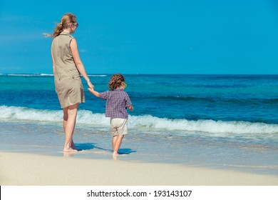 mother and  son standing on the beach in day time