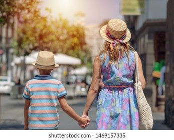 Mother and son in sunhats holding hands and walking by city street.