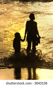 mother and son at sunset in the beach