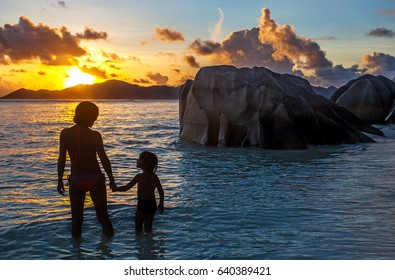 Mother and son in the sunset on the beach, Seychelles