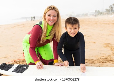 Mother and son with surfboard smiling at camera. Cheerful mother and little son in wetsuits sitting on sand and waxing surfboard at ocean beach. Surfing concept