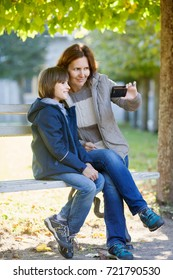 mother and son are take a selfie on a bench in autumn Park