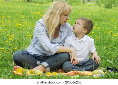 Mother and son talking among dandelion field