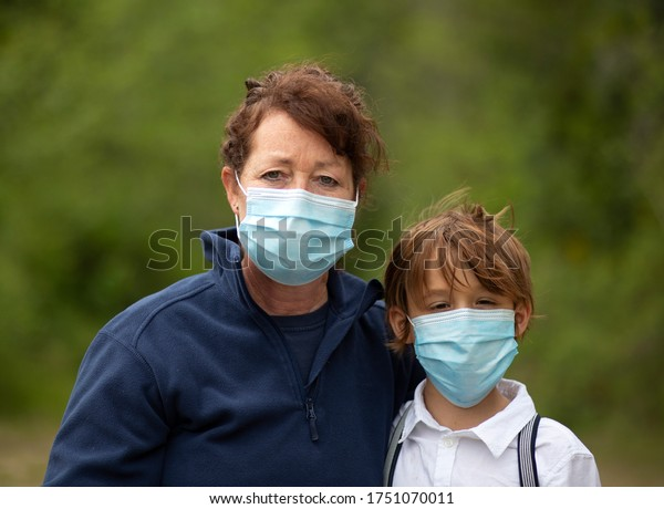 Mother and son together outdoors wearing blue face masks.