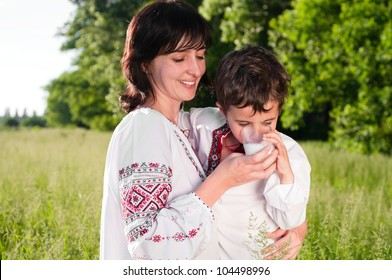 Mother and son in traditional ukrainian shirt drink milk outdoors on the summer meadow