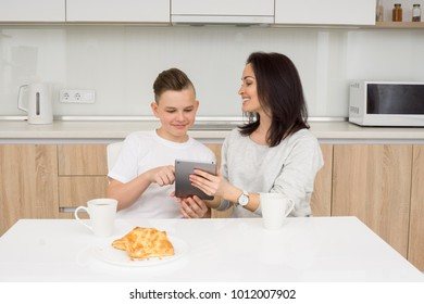 Mother and son using digital tablet together sitting at table in kitchen. Smiling and looking in tablet
