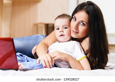 mother and son are using laptop at home