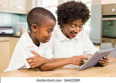 Mother and son using tablet in the kitchen