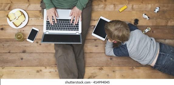 Mor og søn, der bruger tablet og bærbar computer
