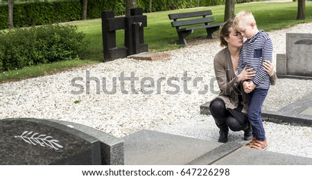 mother and son visiting family grave at cemetery