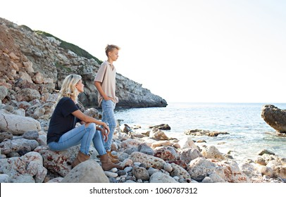 Mother and son visiting rocky beach on holiday, contemplating the sea together on a sunny trip, nature outdoors. Serene family enjoying a holiday day out, healthy travel leisure recreation lifestyle.