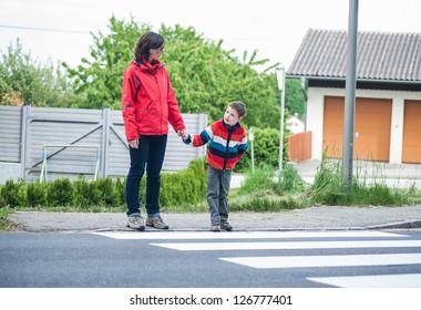 Mutter und Sohn warten auf die Überquerung der Straße