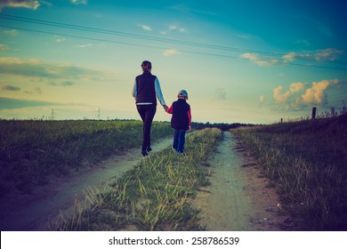 Mother with son walk through rural road