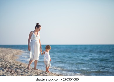 Mother and son walking along beach looking at the sea