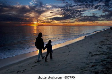Mother and son walking on the beach and watching colorful sunset