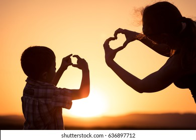Mother and son walking on the field at the sunset time. People having fun outdoors. Concept of friendly family.