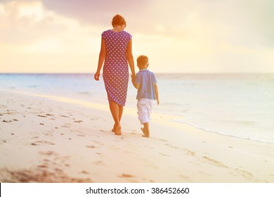 mother and son walking on sunset beach