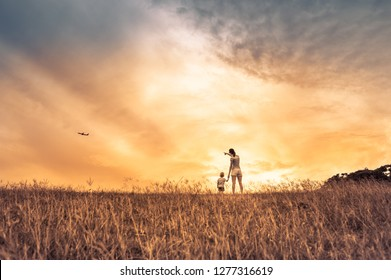 Mother son walking in the park watching a airplane fly by.