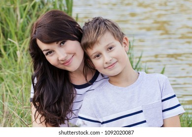 mother and son are walking together, resting near the river, letting paper ships