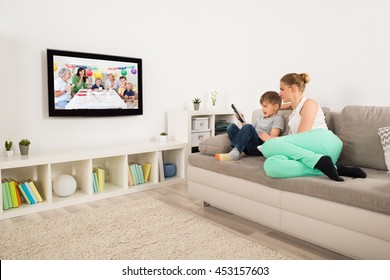 Mother And Son Watching Birthday Celebration On Television At Home