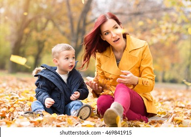Mother and son watching fallen leaves at park