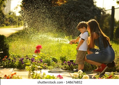 mother and son watering the lawn.