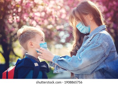 Mother and son wearing face mask. Family going to school during coronavirus outbreak. Safety mask for prevention covid-19. Woman puts on face mask to her child. Stop the coronavirus spreading.