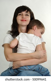 Mother and son in white t-shirts and jeans tightly hugging